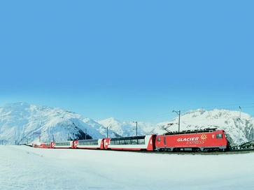 The famous Glacier Express train on its journey across the snowy landscape.