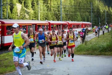 "The runners are cheered on from the ""traveling grandstand"" train along the course."