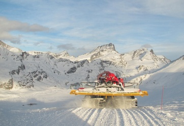 The snow cat team leave the garage just after 4 p.m. In the background stands the Rimpfischhorn.